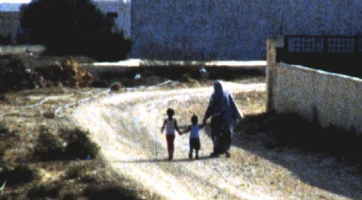 mère accompagné de ses deux enfants sur un le chemin du village